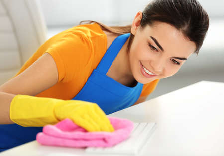 Woman cleaning computer keyboard with duster at table closeup