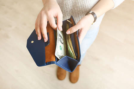 Girl with blue wallet full of money Stock Photo