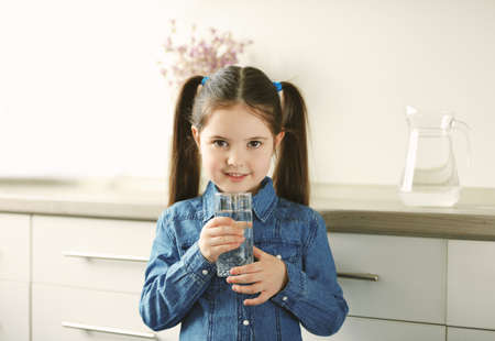 Little girl holding glass of water in living room
