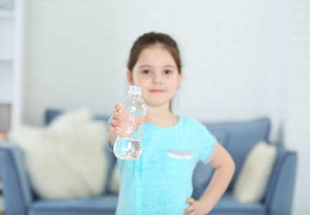 Little girl showing plastic bottle of water in living room