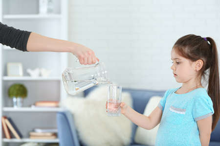 Little girl holding glass and adult woman pouring water from jug in living room Stock Photo