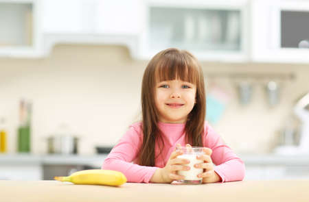 Beautiful little girl having breakfast with milk and banana in kitchen