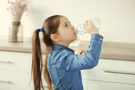 Little girl drinking water from plastic bottle in living room