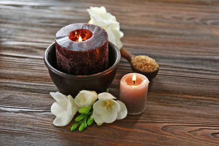 Spa composition with alight candles and beautiful flowers on wooden background Archivio Fotografico