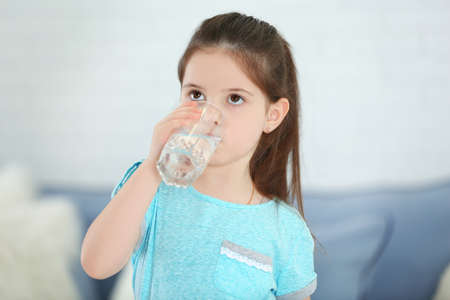 Little girl drinking water from glass in living room