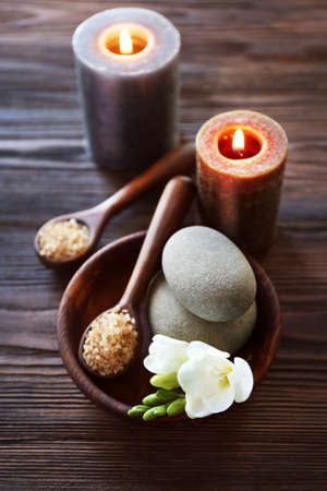 Spa composition with alight candles and beautiful flowers on wooden background Stock Photo
