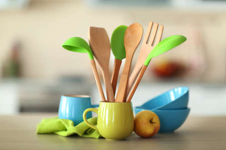 Set of wooden kitchen utensils in green cup with napkin and dishes on the table