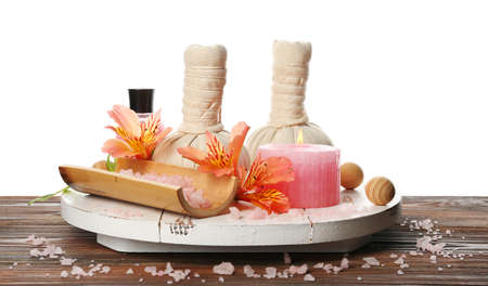 Spa composition with sea salt in a bowl, massage balls and flowers on wooden table against white background