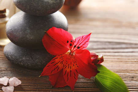 Pebbles and exotic flower on wooden table, close up