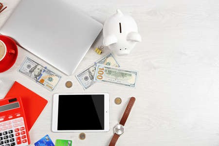Piggy bank, office supplies and money on a white desk, top view Stok Fotoğraf