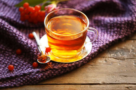 Glass cup of tea, purple blanket and berries on wooden background