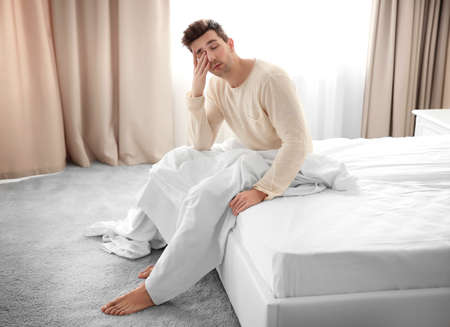 Sleepy young man sitting on a bed. Stock Photo