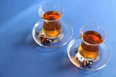 Glass cups of tea on blue background
