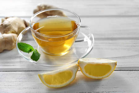 Glass cup of green tea with lemon and ginger root on wooden background