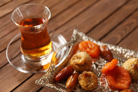 Glass of tea with dried fruits on wooden background