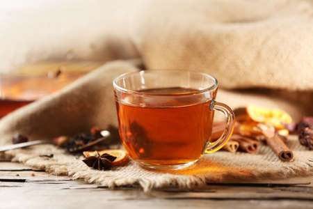 Glass cup of tea with spices on sackcloth background