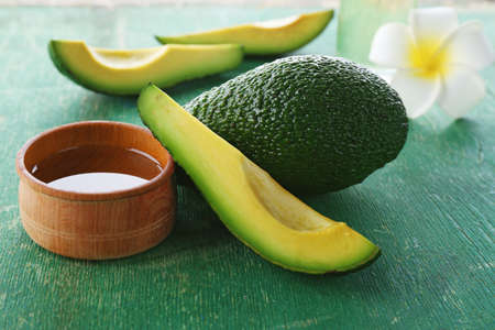 Fresh avocados  on a green table, close up