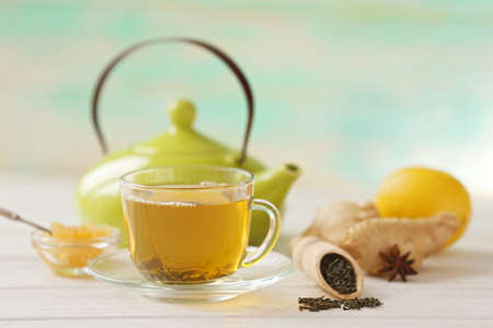 Glass cup of green tea with lemon and leaves on wooden table closeup Stock Photo