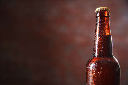 Brown glass bottle of beer on blurred background, close up