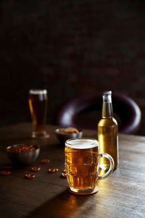 Glass mug of light beer with bottle and snacks on wooden table