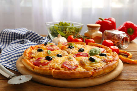 Fresh baked pizza on a wooden table, close up Stock Photo