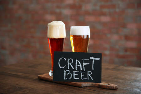 Glasses with different sorts of craft beer on wooden tray Stock Photo