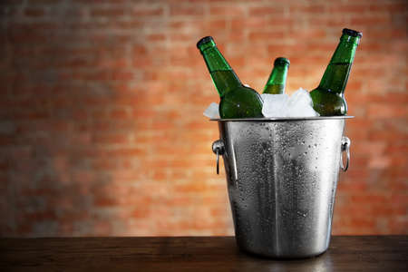 Green glass bottles of beer in ice-pail on brick wall background Stock Photo