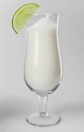 Hurricane glass with granulated sugar and slice of lime on grey background