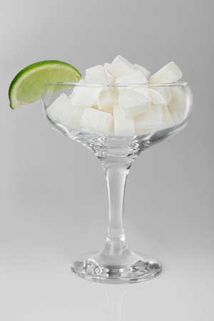Margarita glass with lump sugar and slice of lime on grey background