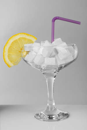 Margarita glass with lump sugar, slice of lemon and cocktail straw on grey background