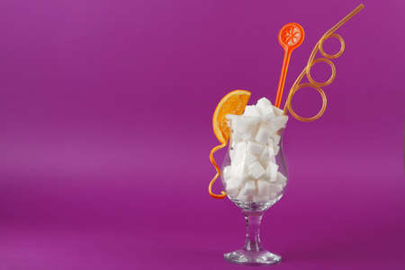Hurricane glass with lump sugar, cocktail straw and orange slice on purple background Stock Photo