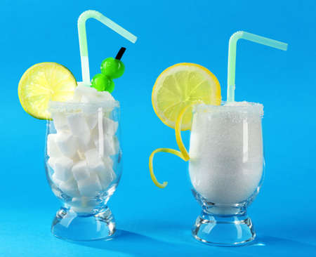 Glasses with granulated, lump sugar, cocktail straws, cherries and citrus slices on blue background Stock Photo