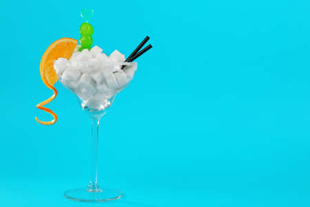 Margarita glass with lump sugar, cocktail straws, cherries and orange slice on blue background Stock Photo