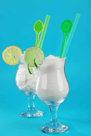 Hurricane glasses with granulated, lump sugar, cocktail tubes and citrus slices on blue background