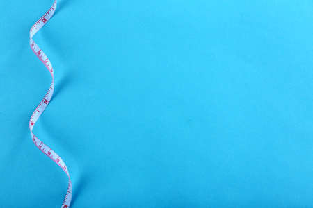White measuring tape on a blue background Stock Photo