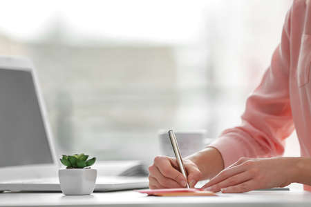 Businesswoman writing with pen in office