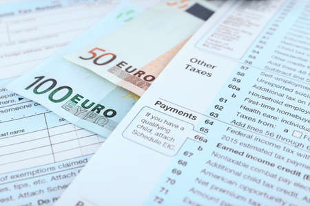 1040 Income Tax Form and euro bills, close up Stock Photo