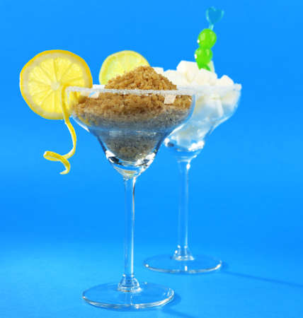Margarita glasses with lump, brown sugar, cocktail cherries and citrus slices on blue background