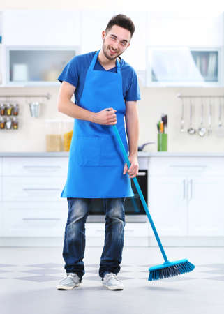 Man sweeping floor in the kitchen Stock Photo