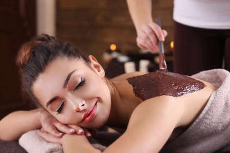 Schönes junges Mädchen , das Kosmetik-Maske im Badekurortsalon hat