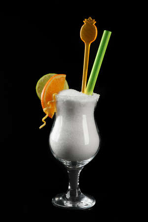 Hurricane glass with granulated sugar, cocktail tube and citrus slices on black background