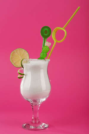 Hurricane glass with granulated sugar, cocktail straw and lime slice on pink background