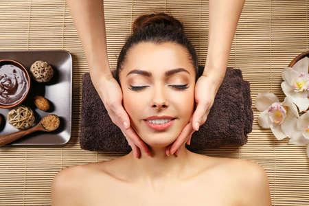 Schönes junges Mädchen , das Gesichtsmassage im Badekurortsalon hat Standard-Bild - 95741131