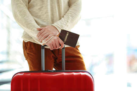 Man holding a large red suitcase and passport, close up Stock Photo
