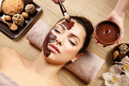 Beautiful young girl getting chocolate mask in spa salon Banque d'images