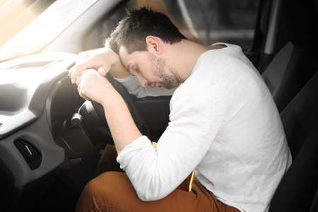 Tired young man asleep on steering wheel in his car.