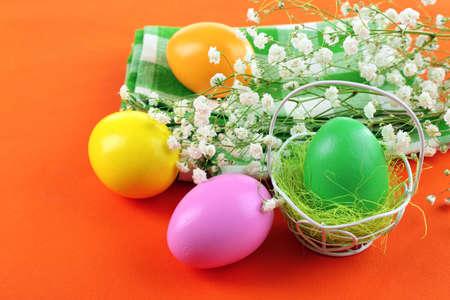 Easter eggs and tulips on napkin, orange background