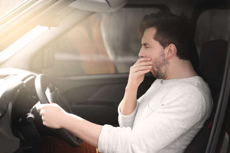 Tired young man driving his car. Stock Photo