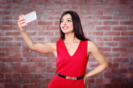 Young attractive girl making photo by her self with mobile phone on brick wall background