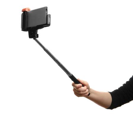 Passi il bastone della tenuta per la fabbricazione della foto con il telefono cellulare, isolato sul bianco